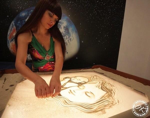 Девушка которая рисует на стекле песком