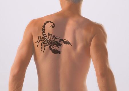 Татуировка на лопатке у девушки - скорпион.